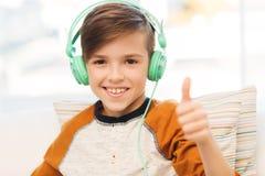 Muchacho feliz en los auriculares que muestran los pulgares para arriba en casa Fotos de archivo libres de regalías
