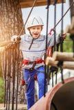 Muchacho feliz en pista de la cuerda en parque de la adrenalina Fotografía de archivo libre de regalías