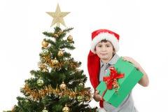 Muchacho feliz en regalo de Navidad de la demostración del sombrero de santa Fotografía de archivo libre de regalías