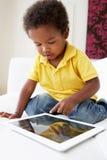 Muchacho feliz en Sofa Playing With Digital Tablet imagen de archivo libre de regalías