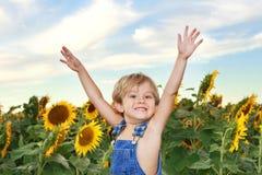 Muchacho feliz en un campo de girasoles Imágenes de archivo libres de regalías