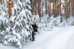 Muchacho feliz en un casquillo de Santa Claus en el bosque del invierno Fotografía de archivo
