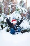 Muchacho feliz en un casquillo de Santa Claus en el bosque del invierno Fotos de archivo