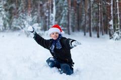 Muchacho feliz en un casquillo de Santa Claus en el bosque del invierno Foto de archivo libre de regalías