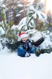 Muchacho feliz en un casquillo de Santa Claus en el bosque del invierno Imágenes de archivo libres de regalías