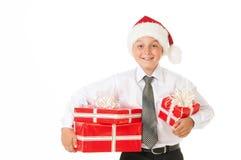 Muchacho feliz en un sombrero de la Navidad con los regalos Fotografía de archivo libre de regalías