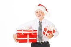 Muchacho feliz en un sombrero de la Navidad con los regalos Imagen de archivo