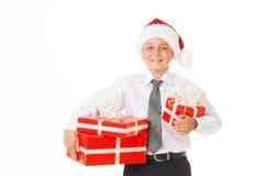 Muchacho feliz en un sombrero de la Navidad con los regalos Foto de archivo libre de regalías