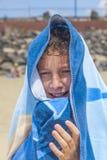 Muchacho feliz envuelto en una toalla en la playa Foto de archivo