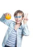 Muchacho feliz hermoso en la camisa azul que sostiene una naranja con una sonrisa de la paja Fotos de archivo