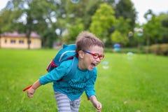 Muchacho feliz joven que corre en la hierba en el parque en un día de verano Imagenes de archivo