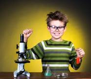 Muchacho feliz joven que realiza experimentos. Pequeño científico. imagenes de archivo