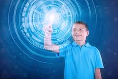 Muchacho feliz joven que trabaja con la pantalla virtual digital Imagen de archivo libre de regalías