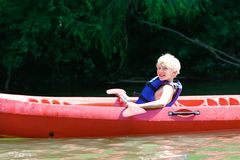 Muchacho feliz kayaking en el río Imagenes de archivo