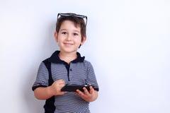 Muchacho feliz lindo que usa el teléfono móvil Niño que juega en smartphone Fotografía de archivo