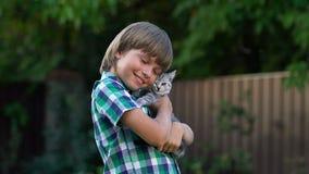 Muchacho feliz que abraza el pequeño gatito, el mejor regalo para los niños, amor blando para los animales almacen de metraje de vídeo