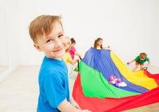 Muchacho feliz que agita el paracaídas colorido con las bolas Fotografía de archivo