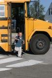 Muchacho feliz que baja del autobús escolar Imagenes de archivo