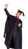 Muchacho feliz que celebra con éxito su graduación Imágenes de archivo libres de regalías