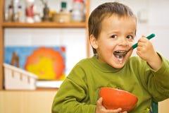 Muchacho feliz que come - cereales Fotografía de archivo