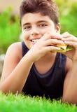Muchacho feliz que come la hamburguesa Fotos de archivo