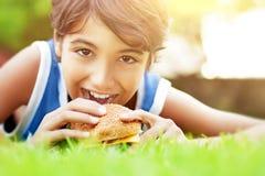 Muchacho feliz que come la hamburguesa Imagenes de archivo