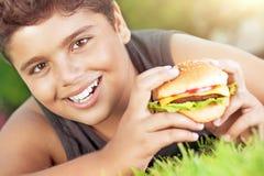 Muchacho feliz que come la hamburguesa Foto de archivo libre de regalías