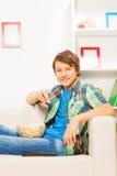 Muchacho feliz que come las palomitas mientras que se sienta en el sofá Imágenes de archivo libres de regalías
