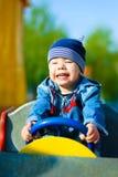 Muchacho feliz que conduce un coche del juguete Imagen de archivo