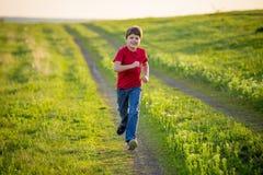 Muchacho feliz que corre en el camino rural con la hierba verde Fotos de archivo libres de regalías