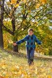 Muchacho feliz que corre en parque soleado del otoño Foto de archivo libre de regalías