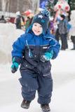 Muchacho feliz que corre en un parque del invierno, Año Nuevo, la Navidad Imagen de archivo libre de regalías