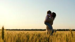 Muchacho feliz que corre a través del campo de trigo La mamá toma al niño en sus brazos y lo besa La familia feliz está abrazando metrajes