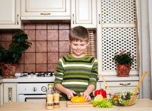 Muchacho feliz que corta una ensalada vegetal en la cocina. imagenes de archivo