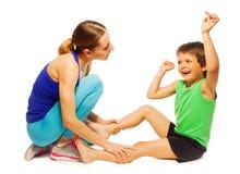 Muchacho feliz que hace ejercicios físicos con el instructor foto de archivo