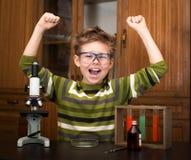 Muchacho feliz que hace experimentos de la ciencia. Educación. fotos de archivo