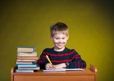 Muchacho feliz que hace la preparación, libros en la tabla. Educatio imagen de archivo