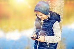 Muchacho feliz que juega al juego en smartphone al aire libre Fotografía de archivo libre de regalías