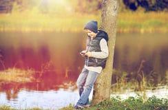 Muchacho feliz que juega al juego en smartphone al aire libre Fotografía de archivo