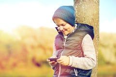 Muchacho feliz que juega al juego en smartphone al aire libre Imagen de archivo libre de regalías