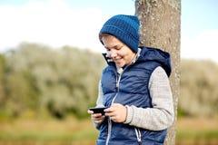 Muchacho feliz que juega al juego en smartphone al aire libre Imágenes de archivo libres de regalías