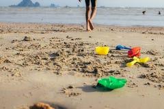 Muchacho feliz que juega el juguete de la playa y que salpica en la playa del mar fotografía de archivo