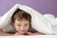 Muchacho feliz que juega en cama debajo de una manta o de una sobrecama blanca Imagen de archivo libre de regalías