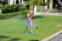 Muchacho feliz que juega en el jardín con el espray de agua Fotografía de archivo
