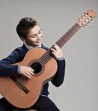 Muchacho feliz que juega en la guitarra acústica Fotos de archivo libres de regalías