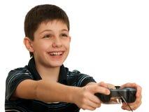 Muchacho feliz que juega un juego de ordenador con la palanca de mando Imagen de archivo