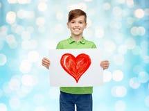 Muchacho feliz que lleva a cabo el dibujo o la imagen del corazón rojo Imágenes de archivo libres de regalías