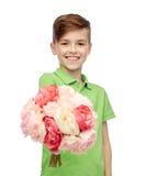 Muchacho feliz que lleva a cabo el manojo de la flor Foto de archivo libre de regalías