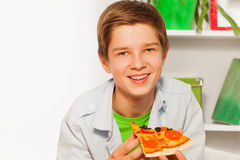 Muchacho feliz que lleva a cabo el pedazo de la pizza y que come en casa Imagen de archivo