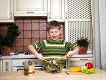 Muchacho feliz que mezcla una ensalada vegetal en la cocina. imagenes de archivo